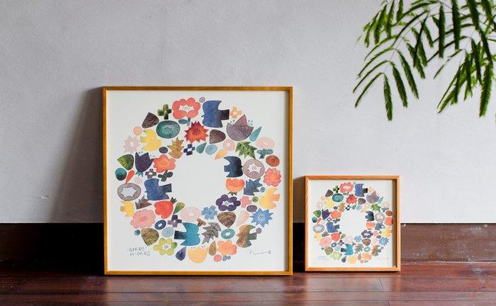 こちらは伊藤さんが描いた水彩画をポスターにしたもの。カラフルな鳥や花たちがリースのように丸く描かれ、とても華やか。  サイズは60cm×60cm(左)、30cm×30cm(右)の2種類。小さい方はポスターのみでも購入可能です。