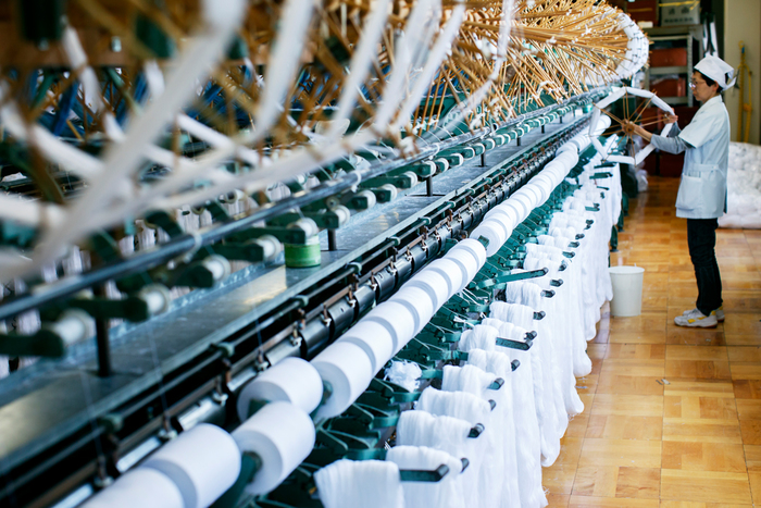 染色工場でシルケット加工・漂白・染色された糸は再び滋賀の工場に送られ、かせからチーズへ巻き直されていきます。これにより、この後製品となる巻きの作業がしやすくなるのです