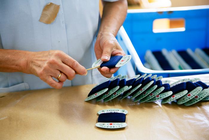 カードに巻かれた糸は、最後までひとつひとつ検品されていきます。写真は、竹串で巻き乱れた糸を内側に入れているところ。機械ではできない繊細なところは、こうして手作業で丁寧に進められていくのです
