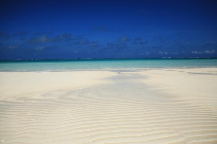 約7キロの長さを誇るハテの浜の白砂の美しさは格別です。抜けるような青空、どこまでも続く透明な碧い海、日射しを浴びてキラキラと輝く白い砂紋が融和した景色は楽園そのものです。