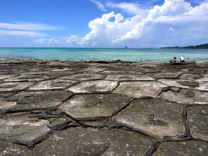 沖縄県の天然記念物に指定されている奥武島の畳石は、久米島有数の景勝地です。透き通る青い海の手前に、直径1メートル以上から2メートルほどの六角形をした巨岩が整然と並び、独特の景観美を作りだしています。