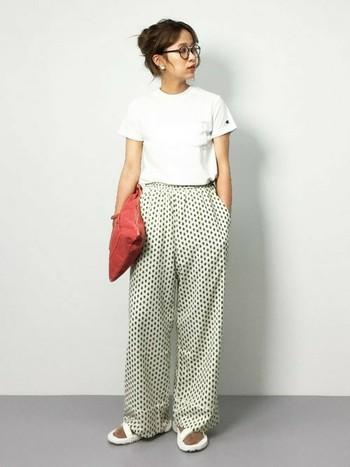 柄モノのパジャマ風ロングパンツに合わせるならシンプルな白Tシャツがオススメ。タックインして脚を長く見せて。部屋着っぽく見せないためにはクラッチバッグなど小物に工夫するのが◎