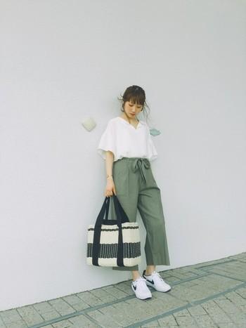白のシャツにカーキのワイドパンツでちょっぴり大人っぽく。タックインしてリボンを見せることでちょっぴりレディに仕上げています。バッグとスニーカーの色を合わせているところもオシャレ。