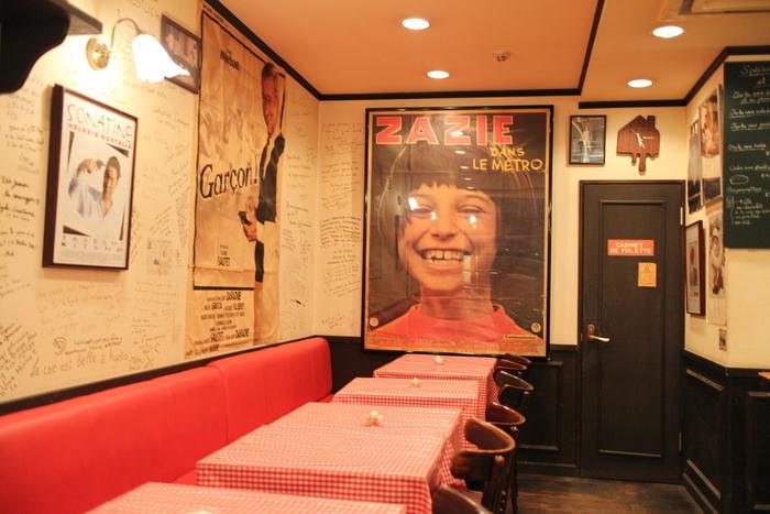 店内もフランスの空気がそのまま感じられるようなお洒落さです。フランス映画のポスターが飾られ、壁には世界中のお客さんからのメッセージが書かれていて、京都在住の外国の方もたくさん訪れるパン屋さんです。 赤いギンガムチェックのテーブルクロスがキュートなイーとインスペースがあり、朝早くからたくさんの人で賑わいます。コーヒーやフランスビールと一緒に、絶品のパンがいただけます。