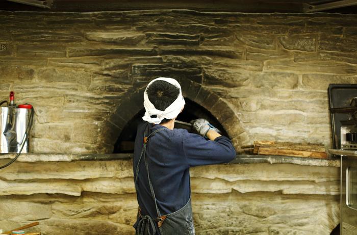 「多分、日本初のロケットストーブの薪窯です」という窯は、平田さん自らが設計したもの。2011年の震災をきっかけに、単一のエネルギーに頼らないパンづくりを目指しました
