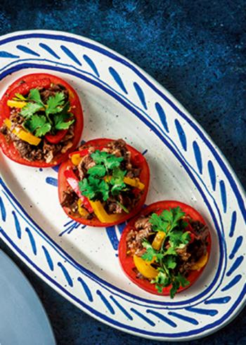 トマトの上に盛りつける、おしゃれなスパイシーサラダのレシピ。お肉ものせて食べごたえ十分!黒コショウのピリリとし辛さに、レモンと香菜の爽やかな香りが食欲をそそります。