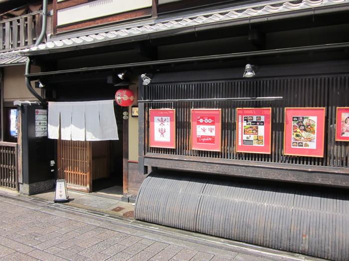 甘味処ぎおん楽楽は、艶やかな着物姿の舞妓さんや芸妓さんが行き交う、京都屈指の華やかな通り、祇園花見小路通に面して店を構えるカフェです。町屋を象徴する意匠「犬矢来」がある甘味処ぎおん楽楽からほど近い場所には、歌舞伎「仮名手本忠臣蔵」にも登場する「一力亭」をはじめ、由緒あるお茶屋さんが軒を連ねています。江戸時代の面影を色濃く残す甘味処ぎおん楽楽の周囲は、数世紀前から時間が止まっているかのようです。