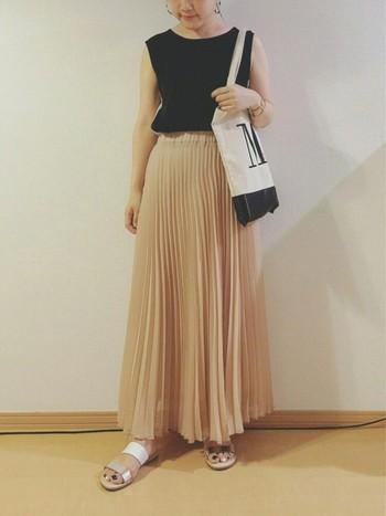 ピンクベージュのプリーツスカートにシルバーのレザーがアクセントのサンダルが素敵。アクセは少なめにまとめると、モダンな雰囲気のコーディネートになります。