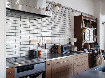 艶感のある白い横長の長方形タイル。シンプルなのにありきたりでないキッチンに仕上がっています。施主がDIYされたという木のキッチン(ホワイトオークの無垢板に変更後、ワトコオイルで塗装をしたそう)と真鍮の把手もすてき!