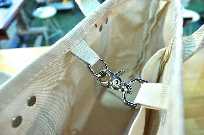 上部はフックになっていて、簡単に口が開くのを止めることができます。出し入れのしやすさと利便性を両立させたデザインです。中には小さなポケットもあり、携帯やお財布などの整理もスッキリできます。
