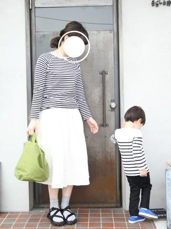 トップスをボーダーでリンクさせた親子モノトーンコーデ。ボトムスは、ママ=白、お子さん=黒であえてお揃いにせず、変化をつけているところがポイントです。グリーンとブルーの差し色も素敵。