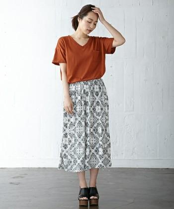 落ち着いたオレンジのVネックシャツを、柄が素敵なスカートと合わせて大人カジュアルに。袖がゆったりしたタイプは、少し折り返して着るとコーデの幅が広がりますよ。