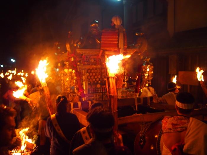 みなぎる活気の中、あかあかと燃える大松明に照らされながらゆっくりと神輿が進んでゆく様は、賑やかでありながらも厳かな雰囲気が漂っています。