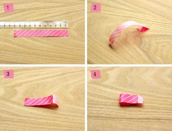 写真のようにマスキングテープを10cmぐらいにカットします。(写真1)  次にテープの端を1cmぐらい残して裏返し、粘着面をペタッと貼り合わせます。(写真2・3)  さらに、折り曲げた端っこを、もう片方の粘着面に少しだけ貼り合わせれば、1つ目のパーツが完成です。(写真4)  この工程を繰り返し、同じものを6つ作って貼り合わせると・・・
