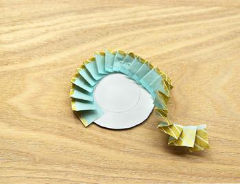 先ほど用意した、直径5cmの厚紙に貼り付けていきます。この時、中に描いた小さな円に沿って貼ると、綺麗な円に仕上がりますよ。