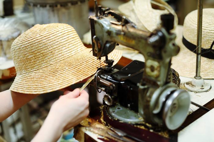 頭部ができあがった後は、角度を変えて筒状に縫います。筒が出来上がると一度型にはめて形を整え、今度は「つば」の部分を縫い進めます。帽子によって手順に差はありますが、これが麦わら帽子の基本的な工程。形の良し悪しを決めるのは、この「帽体縫い」に賭かっているといっても過言ではありません