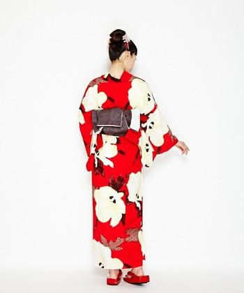 大胆な花柄で街中の視線をくぎ付けにしてしまいそうな朱色の浴衣。帯には柄の一部にも使われているダークカラーを合わせて引き締めれば、バランス良くまとまります。