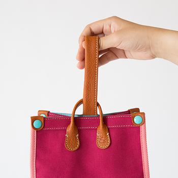 丈夫でなめらかな触り心地のオイルヌメ革の持ち手は、使うほどに風合いが増して自分の色に。持ち手をストッパーにくぐらせる、簡単な開閉方法なので便利です。留め具の付け根にはさりげなく土屋鞄のロゴマークが入っています。