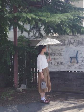 こちらは「イイダ傘店」の日傘。白×ベージュでナチュラルな雰囲気の装いに、やさしい色の傘が上品さを添えています。