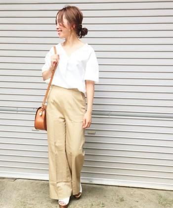 ベージュのワイドパンツに、デコルテが美しく見えるスキッパーシャツを合わせた女性らしいオフィスカジュアルコーデ。白とベージュのカラーは相性が良く、やわらかな雰囲気で好印象。