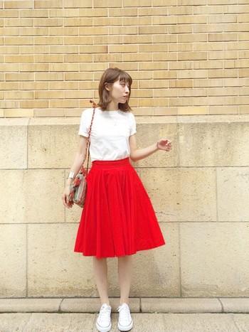 インパクト大の鮮やかな赤のフレアスカート。白スニーカーで、足元の印象を柔らかくすれば、印象がスカートに集中するから、脚に目線がいかないかも◎