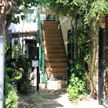 """ショップへとつづく階段。「HOEK」が入居するヴィンテージマンションは緑が生い茂り、表参道の喧騒を忘れるようなひっそりとした佇まい。まさに""""隠れ家""""と呼ぶに相応しい店構えです。"""