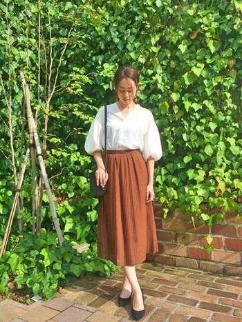 ゆるりとした白シャツをベージュのスカートにインしたコーディネートは、ナチュラルな女性らしさがにじみ出るような品の良いコーディネートに。