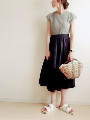 グレーのカットソーを紺色のスカートにイン。トップスもスカートもシルエットはシンプルで、かつ落ち着いたトーンのアイテムをセレクトした、大人のフェミニンコーデ。サンダルとかごバッグで夏らしさをプラスして♪
