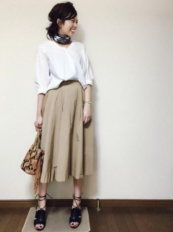 スカーフを首元にくるりと巻くだけで、こんなにこなれ感のある雰囲気に。シンプルなベージュのスカートと白ブラウスを合わせた、レディなコーディネート。