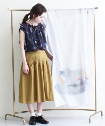 涼しげなデザインが素敵な紺のブラウス。マスタード色のスカートがより印象をひきたてています。