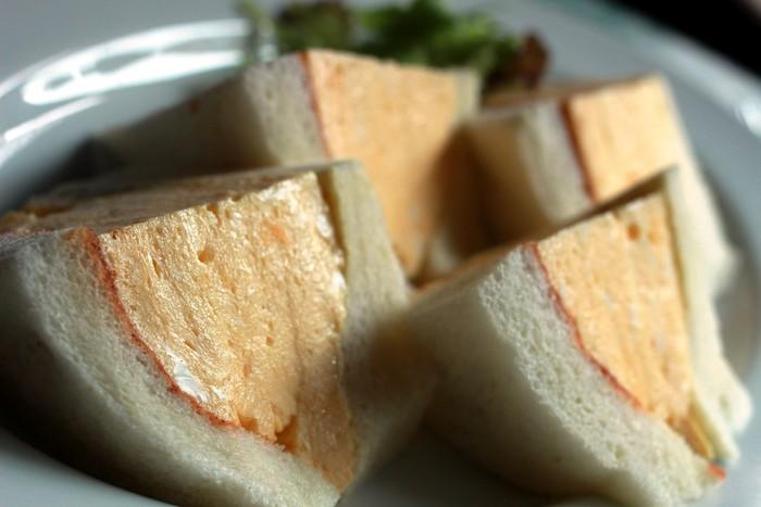 こちらが話題の卵サンド!分厚い卵がぎっしりと詰まった、とってもふわふわのサンドイッチです。 パンもさっくり焼いてあり、食べやすくてボリューミー!  実はこの卵サンドは京都の中では有名な喫茶店「コロナ」の卵サンドをシェフが直伝で伝えて貰ったもの。名前はもちろん「コロナの卵サンド」。 コロナファンも唸る程の卵サンドをぜひご賞味下さい。