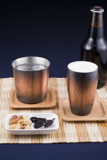 唇と手で冷感を堪能できる銅製のロックカップとタンブラーは、熟練の職人の手仕事によるもの。熱伝導率が高く、カップにも冷たさが伝わります。落ち着きのある渋いカラーと質感で、大人の夏晩酌を始めましょう。  新光金属 [左]純銅手打ち 鎚目ロックカップ \8,000 [右]純銅赤銅仕上げ 鎚目 S型タンブラー(小) \5,000
