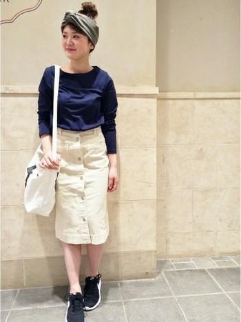 フロントのボタンと両サイドについたポケットがアクセントになった、白のデニムスカート。全体的にタイトめのシルエットですが、裾にかけてややフレアになっていて程よくフェミニンな印象に。