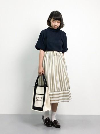 紺色のトップスをインして、コンパクトにまとめたバランスの良いコーディネート。ストライプ柄のミモレ丈スカートが、縦のラインを強調してくれるのでさらにすっきりと見えます。スカートが淡いカラーの時は、トップスやシューズに黒や紺などの引き締め色を持ってくるのがポイント。