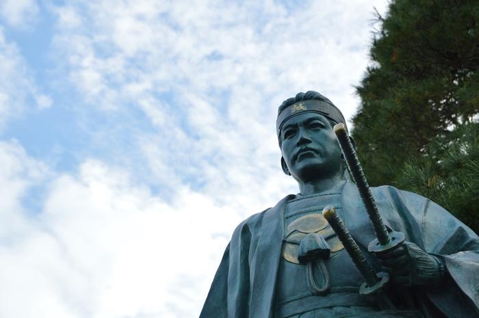 """新撰組は、江戸時代末期に京都の治安を維持する警護活動をしていた集団です。""""新撰組""""と聞くと、自然と浅葱色をしただんだら模様の羽織を想い描く方も多いのではないでしょうか。実は、「浅葱色のだんだら模様」は、新撰組にとって大変重要な意味があります。だんだら模様は、主君の仇打ちを遂げた忠義の象徴でもある忠臣蔵の赤穂浪士にちなんだものです。また、浅葱色とは、武士が切腹するときに身につける着物の色です。すなわち、新撰組の隊士達は、「死を覚悟し、忠義を尽くす」覚悟を決めて厳しい隊務に臨んでいたのです。  新撰組が活躍した江戸時代末期は、厳しい身分制度で統治されていました。新撰組局長の近藤勇と、副長の土方歳三は共に農民身分でありながら幕臣にまで登りつめた人物です。幕府軍と維新志士の間で大きく揺れ動いた江戸時代末期の日本で、最後まで幕府軍として戊辰戦争を戦い、散って行きました。日本を守るべく、奔走した熱き志をもった若者たちの足跡を辿ってみませんか?"""