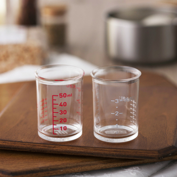 昔なつかしいビーカーのようなデザインのカップは、貝印が料理研究家の脇雅世さんと一緒に手がけた50cc用の計量カップです。 味の決め手となる調味料の分量って、料理をする中でも気の抜けない作業ですよね。大きな計量カップでは計りにくい50ml以下の計量と、大さじ3・小さじ6までの計量ができる便利なアイテムで、大さじや小さじを計量スプーンで何度も計りながら入れる作業が、この計量カップでは1回で出来ちゃいます。