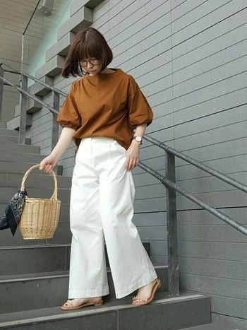 コクーンシルエットが可愛い秋色ブラウンのブラウスも、白のワイドパンツとのスタイリングなら暑い時期でも爽やかな雰囲気に。バーキン風カゴバックとビジューサンダルが涼しさを演出しています。