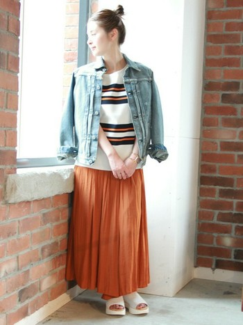 トップスと同系色のオレンジのマキシスカートを合わせたら、秋の定番アイテム、デニムジャケットを肩掛け。まとまり良い秋のスタイルに仕上がっていますね◎