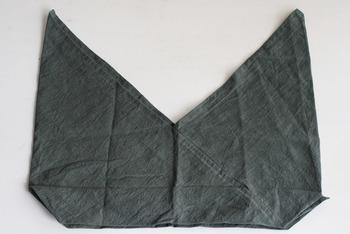 広げるとこのような独特な形をしています。上部をキュッと結んで持ち手にします。中身の大きさによって自在に加減ができ、長めに結べば肩掛けにも。