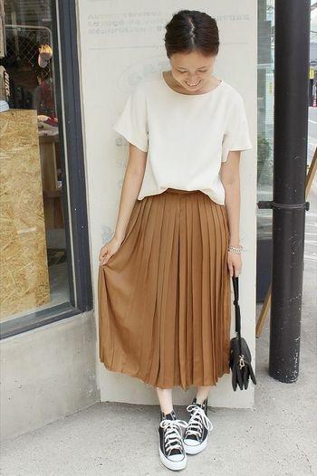 薄いテラコッタカラーのプリーツスカートに白のゆるっとトップスの組み合わせ。小物は黒で統一して、コーディネートを引き締めています。