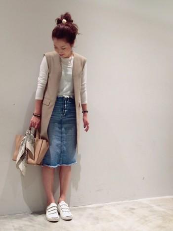 カットソー+デニムスカートのシンプルな上下に、ベージュのベストを羽織るだけで、こんなにもオシャレな着こなしに。ロングベストはタイトスカートを履くと目立ってしまうヒップラインを隠してくれるので、スタイルアップ効果も!