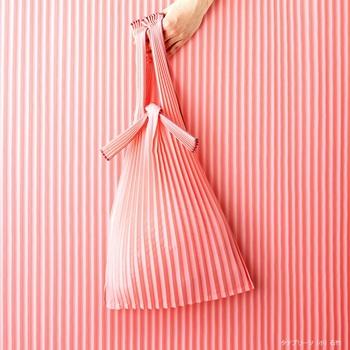 レジ袋風のバッグに早変わり♪  布地に縦のプリーツ加工を施すことで、折りたためば細く小さく、広げれば収納力抜群と、機能性の高いバッグに仕上がりました。 薄手なのにとても丈夫で、エコバッグにはもってこいのアイテムなんです。