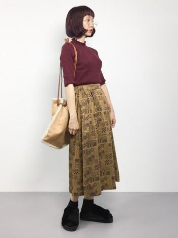 点と線で描いたアートな雰囲気のAラインスカートにワインレッドのトップスを合わせたちょっとレトロなコーディネート。足元にファーサンダルを合わせれば、ボリュームがと秋らしさがプラスされます。