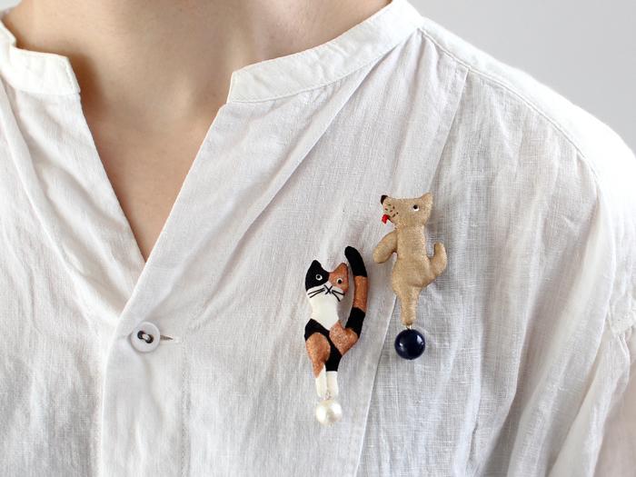 こちらはユニークな表情に目が釘付けになりそうな、玉乗り猫と玉乗り犬のブローチ。 ちょっととぼけたお顔がかわいいですね。 シンプルなシャツに二つ合わせて着ければ、コーディネートの主役になります。