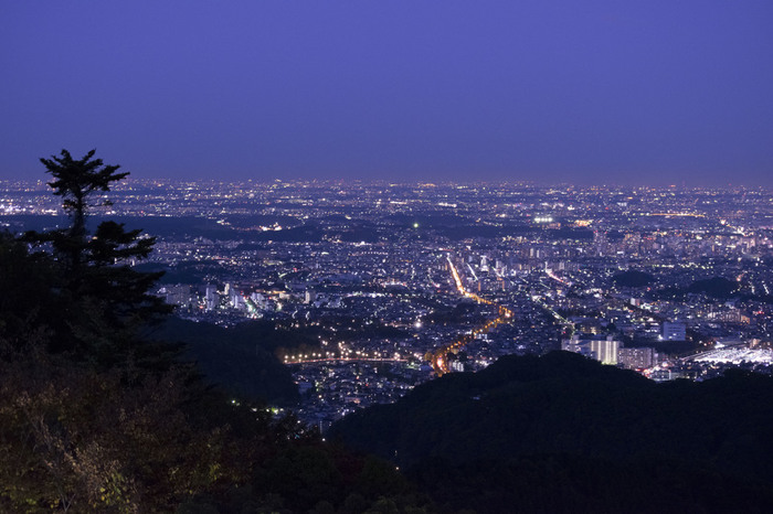高尾山の山頂からは、東京都八王子市を一望することができます。特に夜景の美しさは格別です。藍色の夜空と暗闇の中から浮かび上がる家々の灯りや街燈の光が融和し、紺色のベルベットに宝石をちりばめたような美しい景色が広がっています。