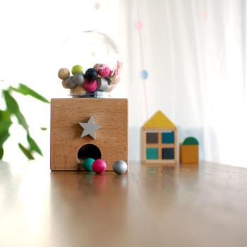 木とビビットな色合いを組み合わせたおもちゃブランド「kiko+(キコ)」のぬくもり溢れる小さなガチャガチャマシーン。  中身のピースも木でできています。