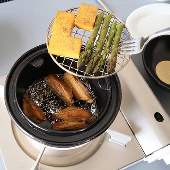 作り方は、鍋にアルミホイルとチップを敷き、網をセットして具を乗せるだけ。途中で水差しが必要ですが、そこを含めてもとっても簡単なので、燻製が好きな人にはたまらないかも。 中は2段になっているので、同時にいくつもの食材が作れるのは嬉しいですよね。