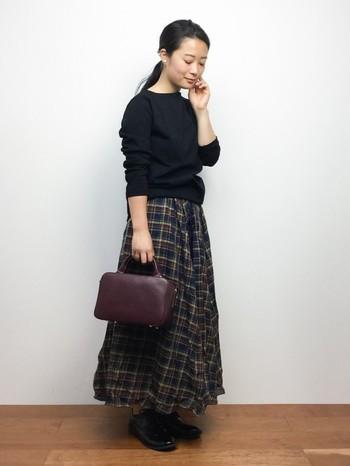 あたたかみのあるチェック柄のフレアスカートにレザーバッグ。落ち着きのあるカラーでまとめたノスタルジックスタイルです。