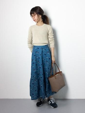 ショート丈のニットにマキシスカートを合わせて、バランス良くコーデしています。シックな色でまとめがちな秋ファッションですが、華やかな総プリント柄をプラスするのも◎