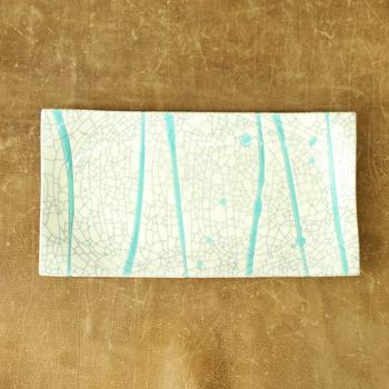 貫入に染み込ませた墨が模様のように広がるお皿です。流しかけられたターコイズの釉薬が無作為で味のある表情を添えていますね。